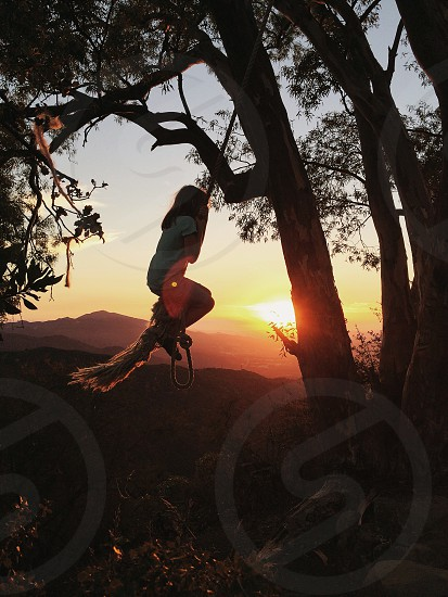 young girl swings on rope at sunset photo