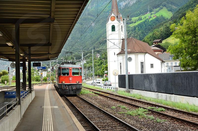 FLUELEN SWITZERLAND - JULY 4 2014: Train Platform. A train comes in at the platform in Fluelen Switzerland on Lake Lucern. photo
