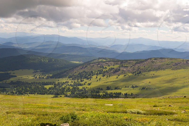 Landscape of green valley flooded with light with lush green grass mountains covered with stone and hills a fresh summer day under a blue sky with white clouds and sun rays in Altai mountains photo