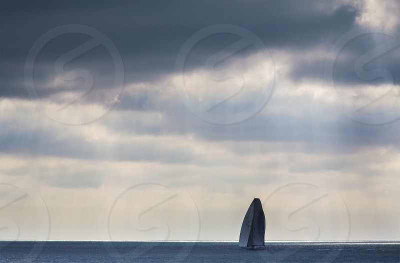 A solo yacht at sea under a moody rain-filled sky- UK Isle of Wight photo