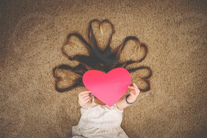 red paper heart on a girl with heart shaped hair photo