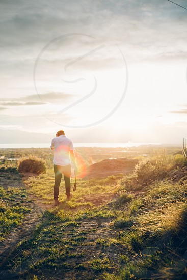 person in white t shirt walking on green grass field by the sea photo