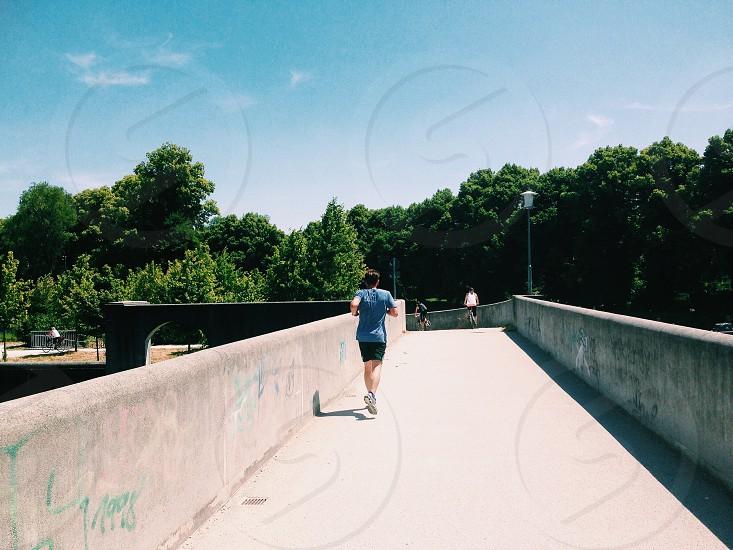 person running on concrete bridge photo