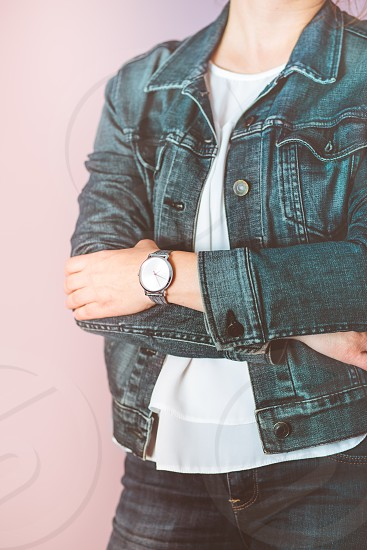 Woman wearing silver wristwatch and jeans jacket. Standing in front of pastel pink wall photo