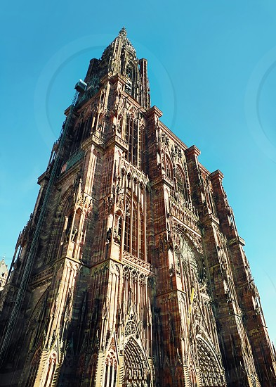 The tower of Roman Catholic Cathedral Notre Dame of Strasbourg in Alsace France. Beautiful sunny day with clear blue sky. Majestic gothic architecture. photo