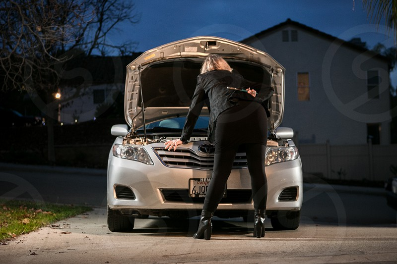 A woman works on the engine of her silver sedan with channel locks while wearing a business casual outfit during twilight. photo