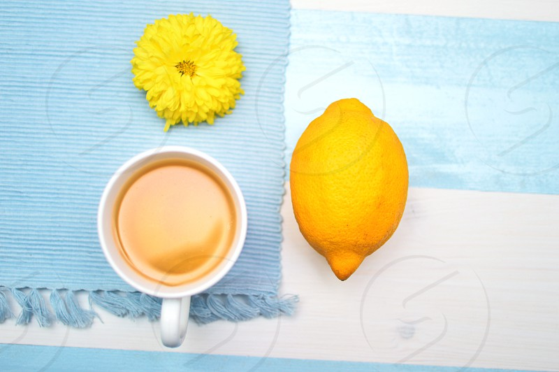 photo of lemon beside white ceramic mug with brown content under yellow petaled flower on top of blue and white surface photo