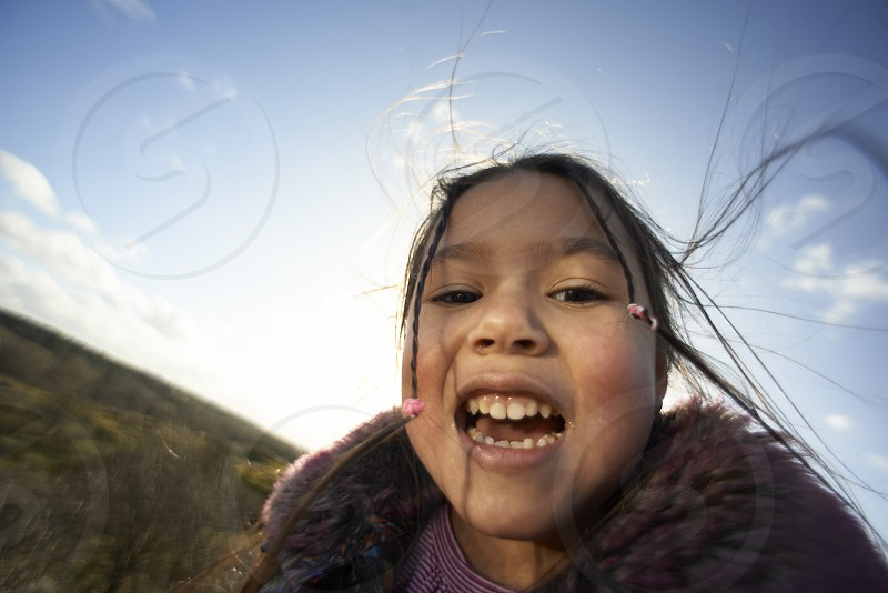 Extreme close up portrait of an Asian girl on a hill during a hiking trip smiling into camera photo