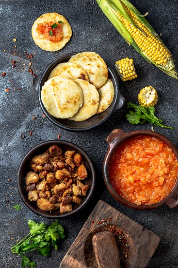 COLOMBIAN traditional food. Chicharron maize arepas with tomato and onion sauce. photo