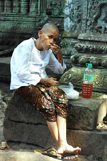 woman in white long sleeve button up top near eating a rice in a plastic pack sitting in a rock photo