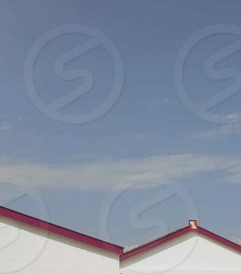 white structure with red roofing under blue sky photo