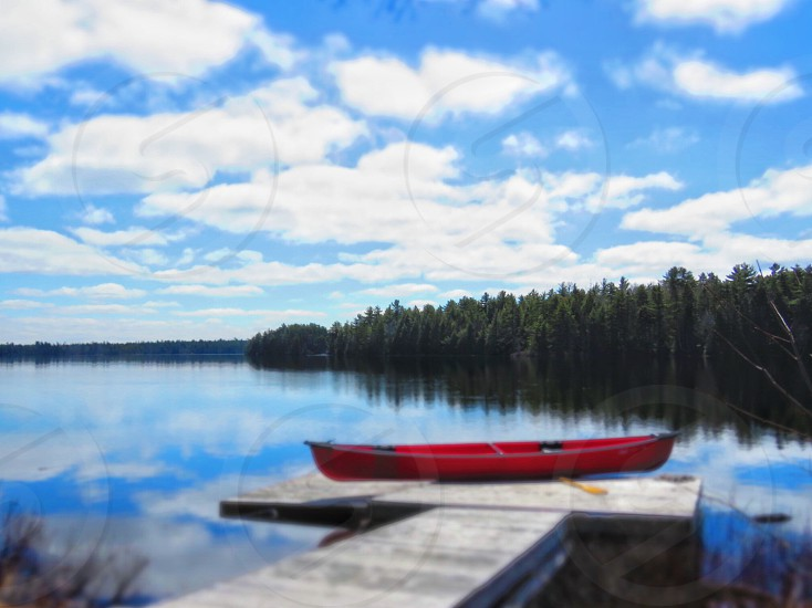 A canoe sitting on a dock awaiting summer fun! A lifestyle including nature. photo