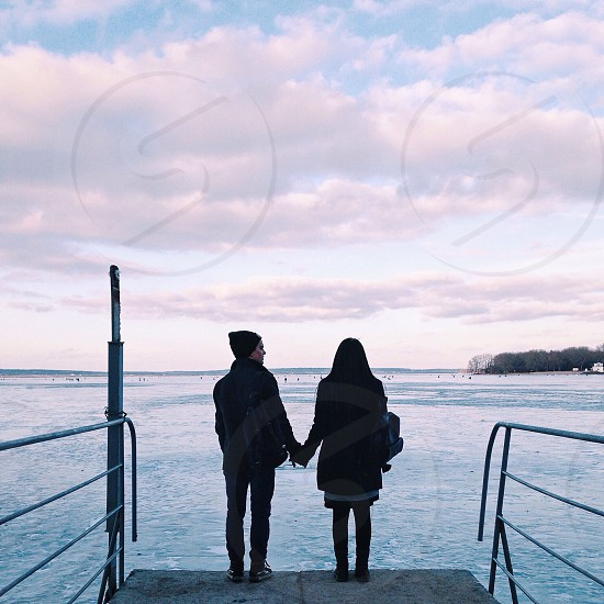 couple holding hands while standing on dock facing body of water photo
