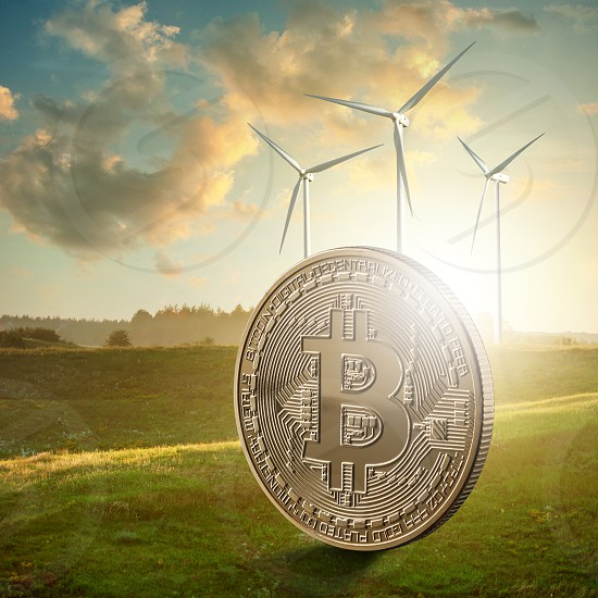 Gold coin bitcoin against the background of a green field and blue sky. The photo can be used in blockchain ICO projects on the ecology and nature. Modern eco and crypto concept for video and site covers photo