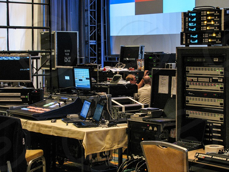 Two technicians adjust gear for a live event surrounded by backstage audio lighting and control equipment. photo