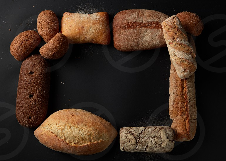 Different kinds of bread isolated on black background. Frame of loafs represented one after another. White and black bread with blank space in middle. photo