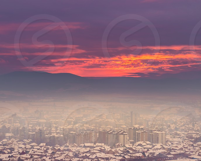 Distant cityscape of Pirot Serbia covered by snow and mist and beautiful colors of sunset sky photo