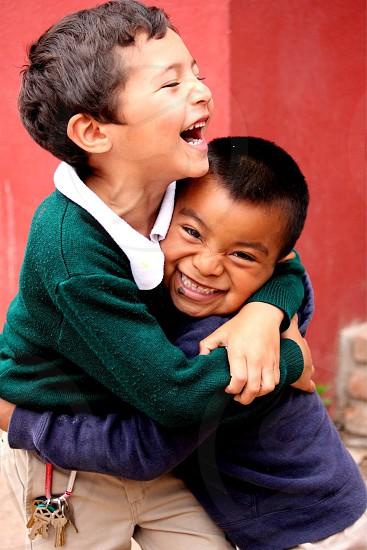 boy in blue hugging boy in green smiling near red walls photo
