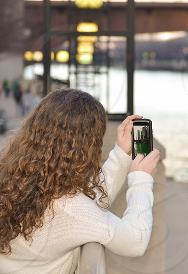 woman holding black android smartphone while taking a photo of a river during daytime photo