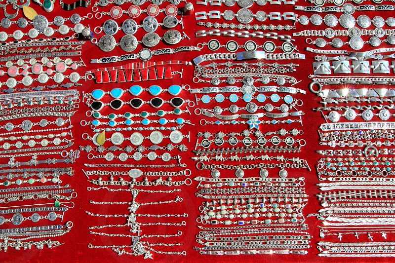 Mexican silver jewellery rows on red background Mexico photo