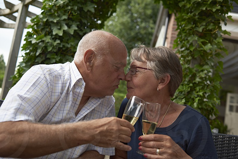 Wealthy elderly caucasian couple celebrating their 50th wedding anniversary with a glass of Champagne and a romantic kiss photo