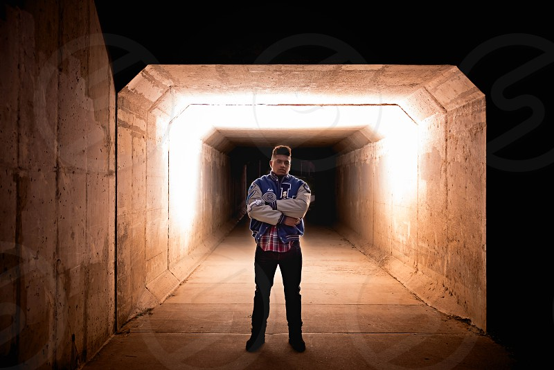 Senior high school boy with dramatic lighting in a tunnel. Wearing his letterman's jacket arms crossed. photo