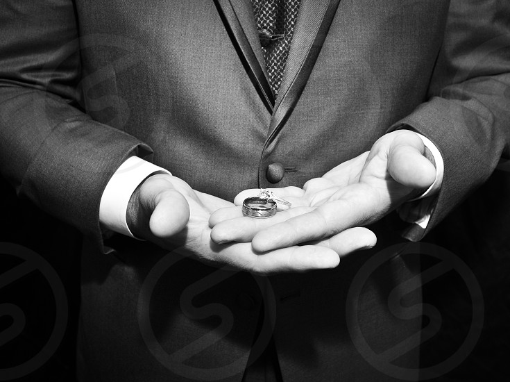 Groom on wedding day holding their wedding bands before the ceremony. photo