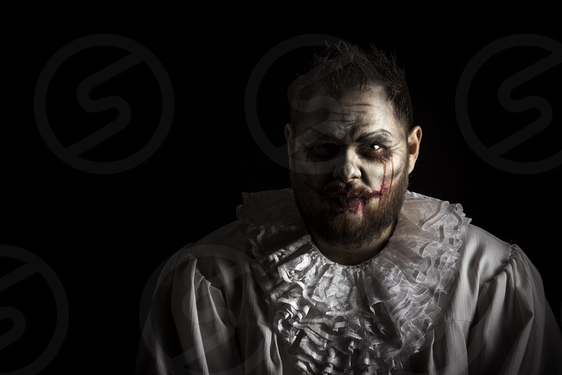 Portrait of a Scary Evil Clown.  Studio shot with horrible face art photo