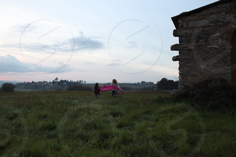 2 girls running on green field with pink kite photo