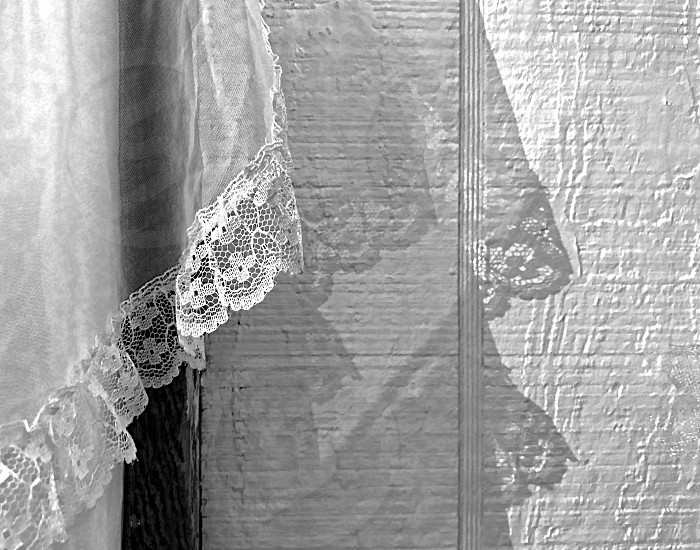 The edge of a sheer lace curtainhangs over a white wall. photo