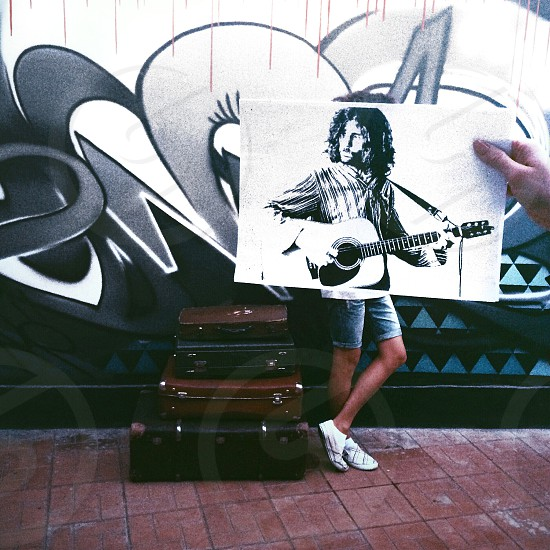 picture of a man playing guitar held up over a man standing in front of a mural photo