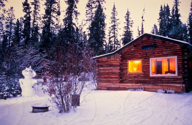 Cozy log cabin fully illuminated in snowy winter with snowman at watch photo