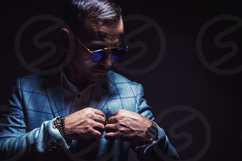 Portrait of an adult man blue striped jacked and blue sunglasses.  photo