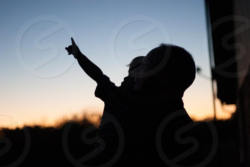 man carrying kid pointing upwards photo