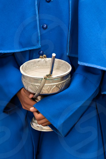 A boy holds a metallic container with holy water during a religious ceremony photo