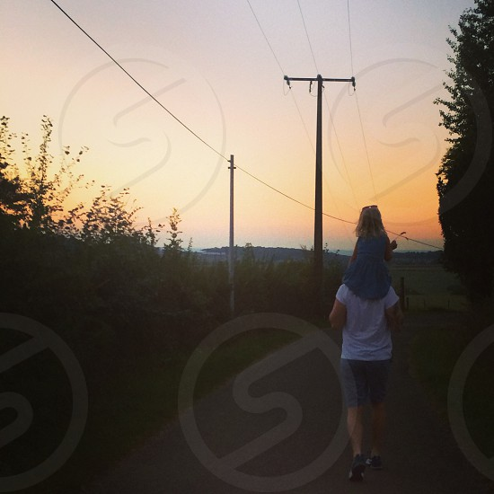 Young girl on dad's shoulders walking to the sunset  photo