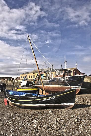 Fishing boats on dry sand in Scottish fishing village. photo