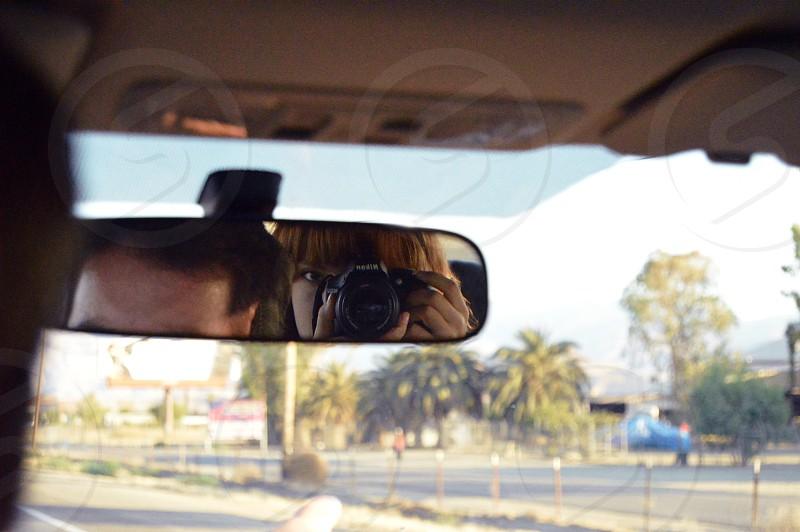 woman taking photo of rear-view mirror inside car photo
