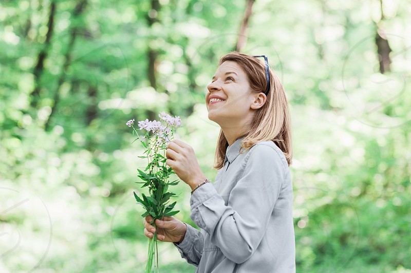 Young woman picking flowers outside in nature photo