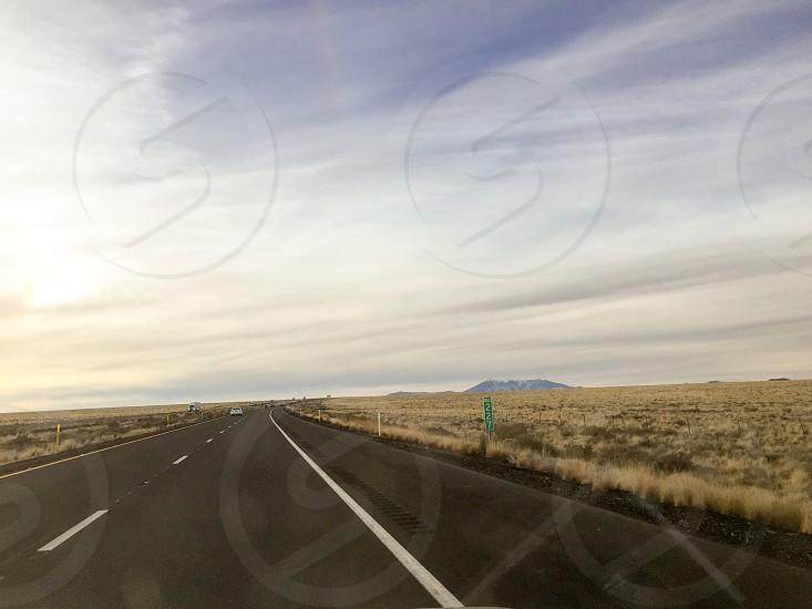 road in between brown grass field photo