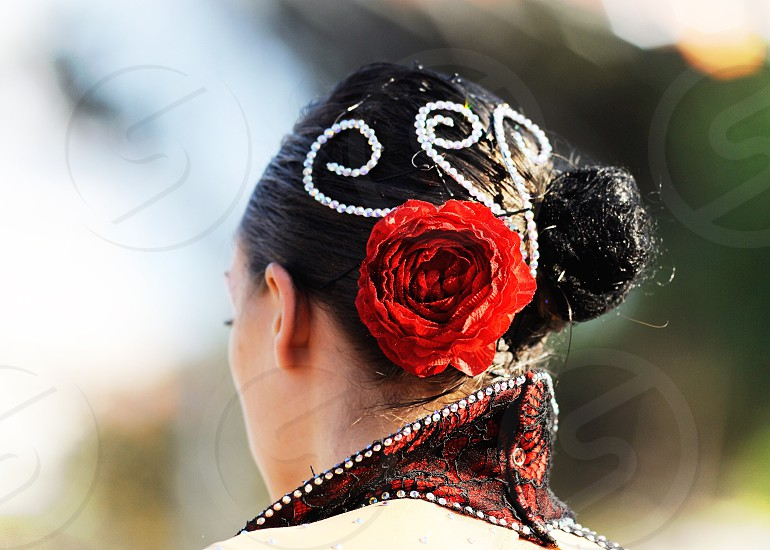 woman with red rose on her hair with white beads photo