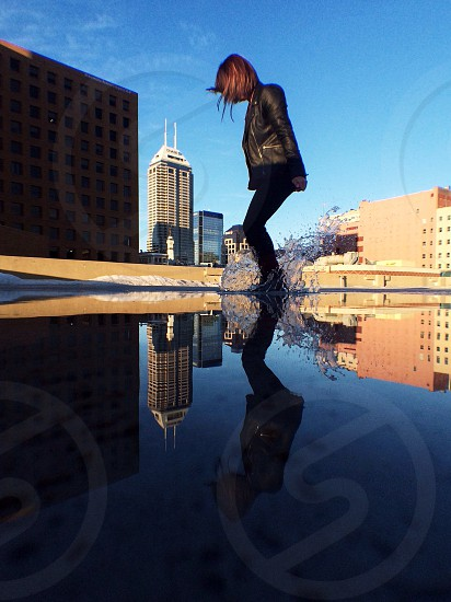 girl splashing in puddle on roof  photo