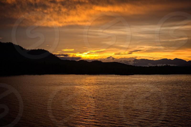 sunset view on horizon and sea beside mountain photo