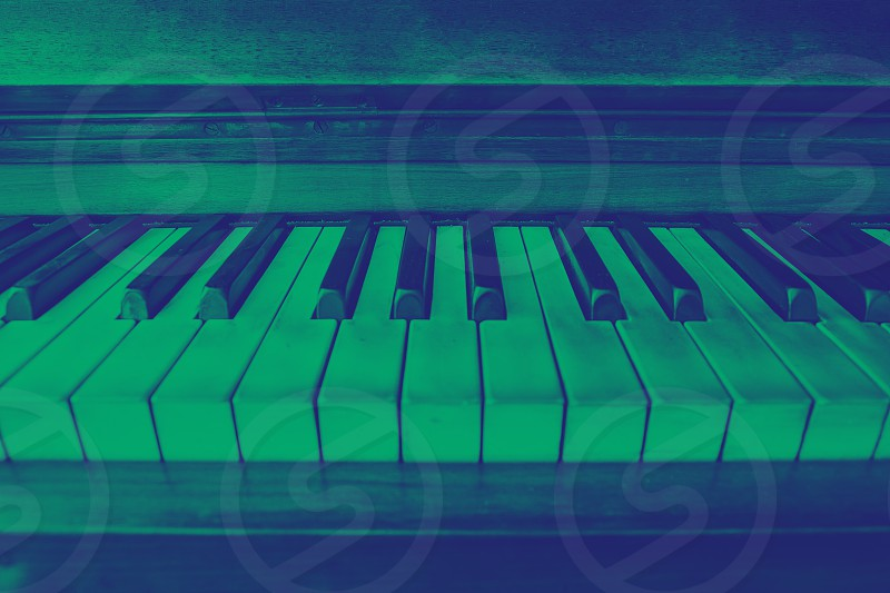 close-up view of the keys of a ancient ruined piano. Green and blue duotone effect photo