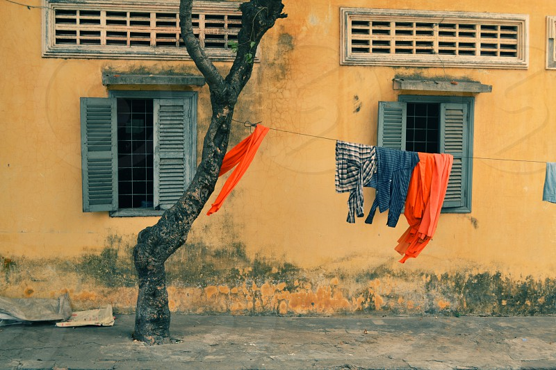 monk monks orange clothes cloths wall monastery dry laundry tree temple street windows cambodia phnom penh asia photo