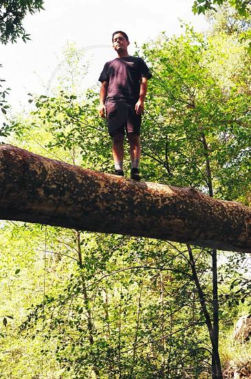 man standing on tree trunk photo