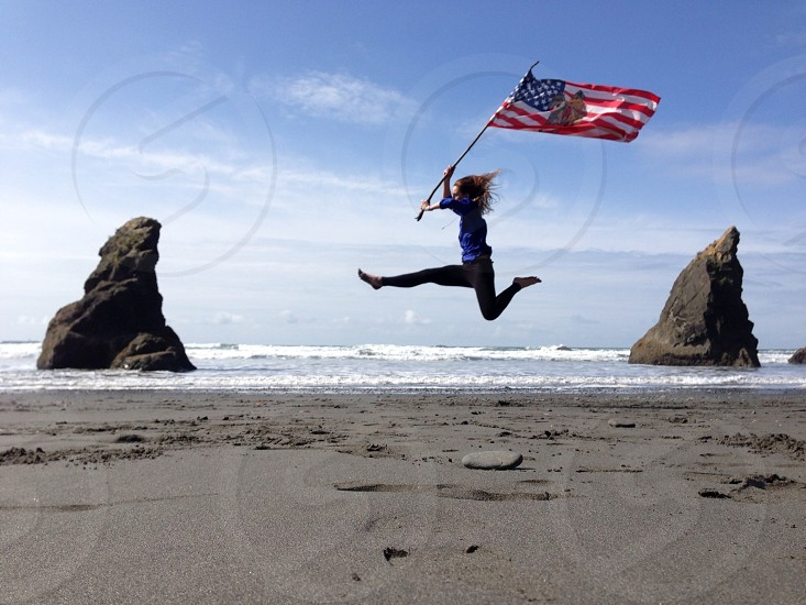 Girl jumping with American flag photo