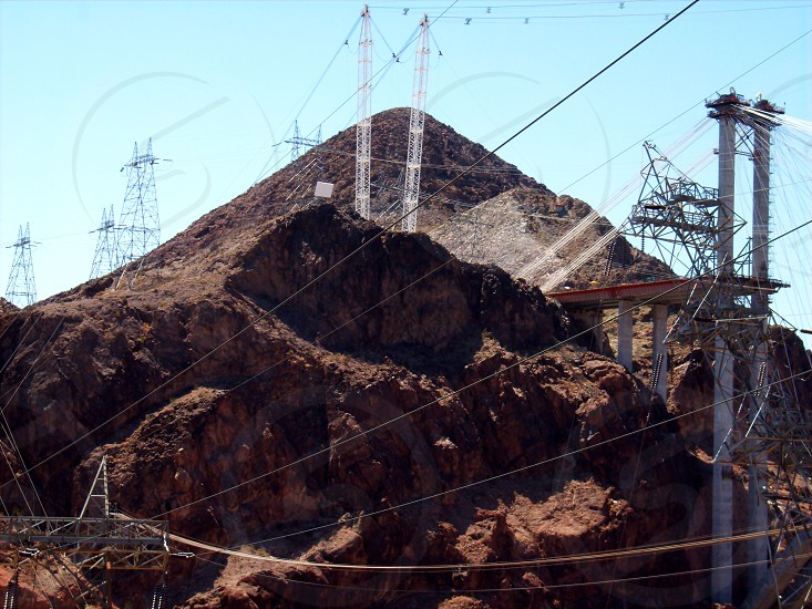 transmission towers and power lines below blue sky during daytime photo