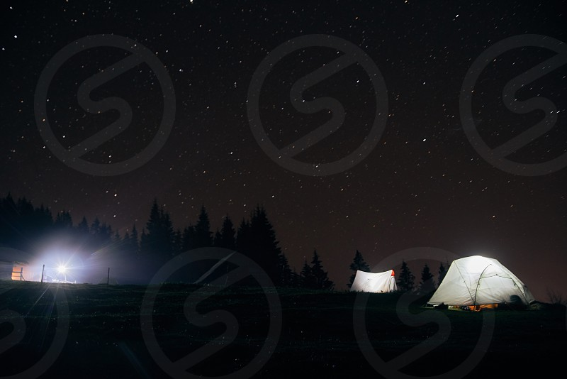 Camping under the stars at night in mountains Illuminated tents Carpathians photo