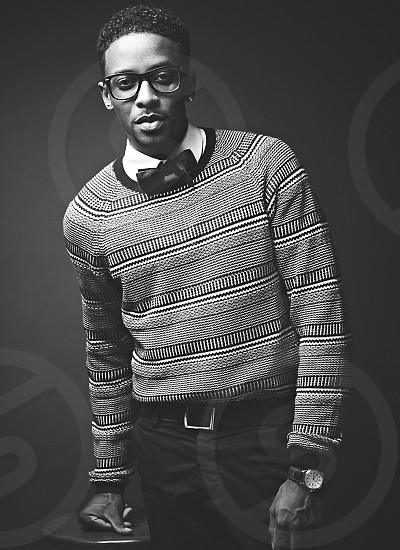 man in black and white striped paneled sweater with white collared shirt black bow tie glasses belt and black pants and watch leaning on wooden stool photo